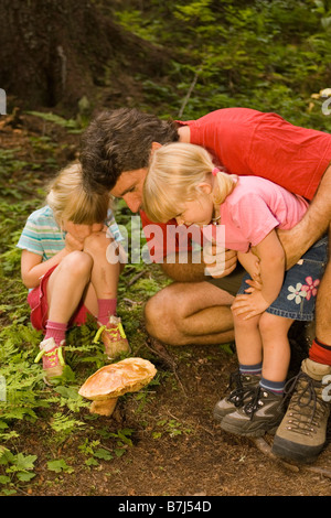 Young man examines mushroom with daughters during hike at Island Lake Resort, Fernie, British Columbia, Canada. - Stock Photo