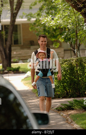 Man walking down street carrying baby in snuggly, Regina, Saskatchewan - Stock Photo