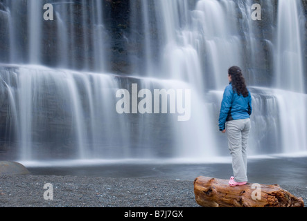 Woman (20-25) standing on a beach log in front of a waterfall - Stock Photo