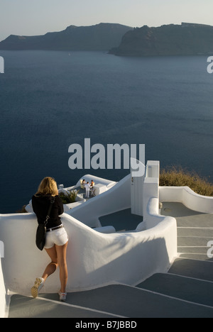 Greece, Santorini, Oia. A tourist looks out to sea from the cliff of Oia - Stock Photo