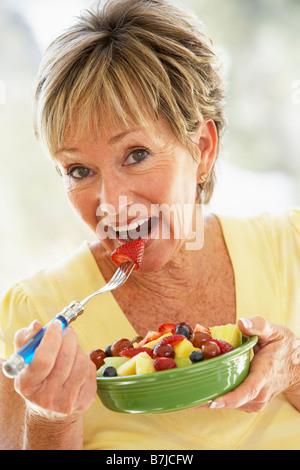 Senior Woman Eating Fresh Fruit Salad - Stock Photo