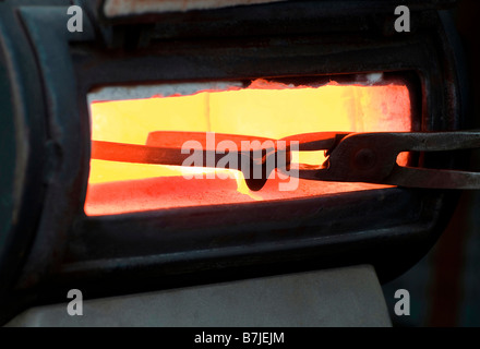 farrier holding hot horse shoe in furnace - Stock Photo