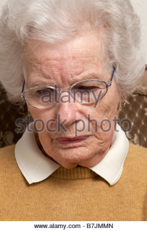 A portrait of an old woman sitting in a chair looking worried. - Stock Photo