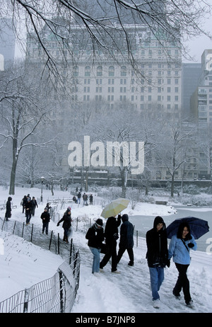 New York City People in Central Park During a Snowstorm View of the Plaza Hotel USA - Stock Photo