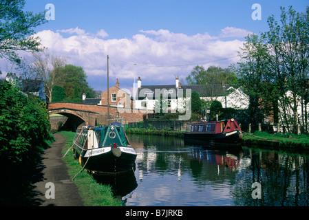 Bridgewater canal Moored boats Bridge Houses Trees LYMM CHESHIRE ENGLAND - Stock Photo