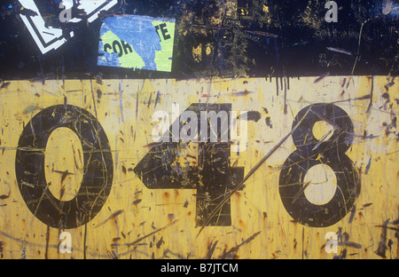 Detail of side of metal tank once yellow and black but now heavily scratched with 048 painted on it and torn notices - Stock Photo