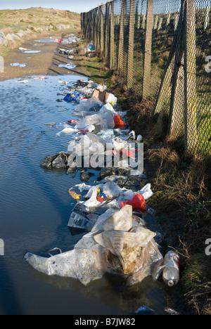 Rubbish outside perimeter fence of landfill site. - Stock Photo