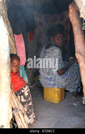 Mother and child cooking inside a shelter State House IDP camp Hargeisa Somaliland Africa - Stock Photo