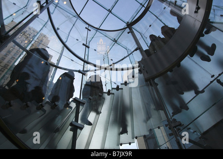Customers walking up and down the glass steps at the Apple Store on Fifth Avenue in New York City - Stock Photo