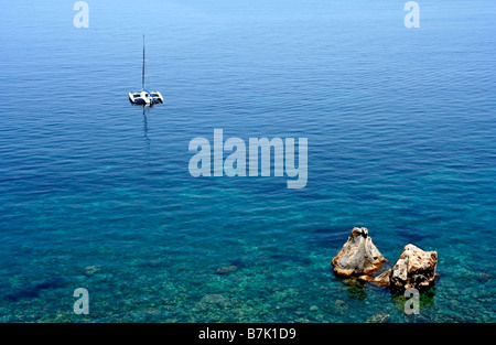 Catamaran and rocks in Scilla, province of Reggio Calabria, region of Calabria, southern Italy, on Messina Straits - Stock Photo
