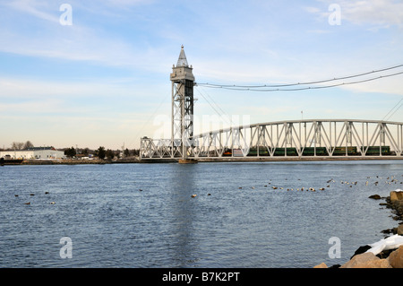 Train engine with cars crossing the Cape Cod Canal on the railroad bridge which raises and lowers for passage across - Stock Photo