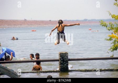 Girl jumps off fence post into water of lake. - Stock Photo