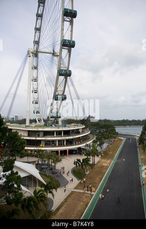 the Singapore Flyer in Singapore, with the Formula One Grand Prix track running by it. - Stock Photo