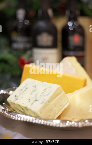 Bricks of blue, cheddar, parmesan, and brie cheese in a silver dish with bottles of port in background - Stock Photo