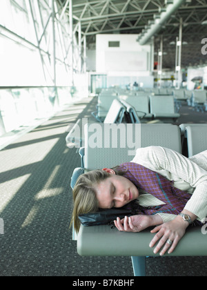 woman sleeping on bench in airport - Stock Photo