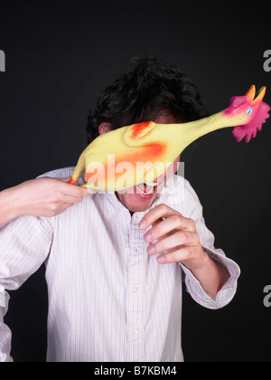 man getting hit with rubber chicken - Stock Photo