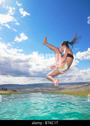 Woman jumping in swimming pool - Stock Photo
