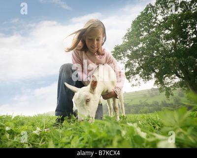 Girl Holding Goat - Stock Photo