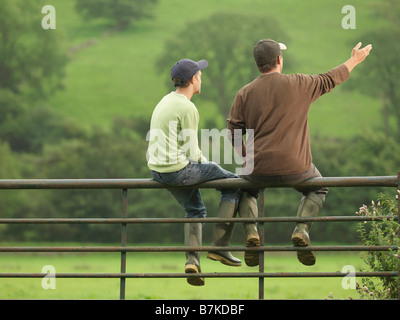 Farmer Talking To Son On Gate - Stock Photo