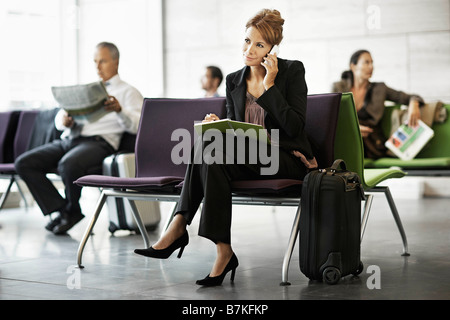 Woman with suitcase, on the phone - Stock Photo