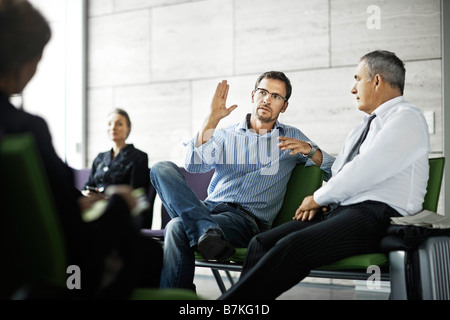 Men talking in waiting room - Stock Photo
