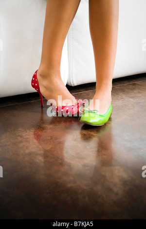 Cropped view of woman wearing mismatched shoes - Stock Photo