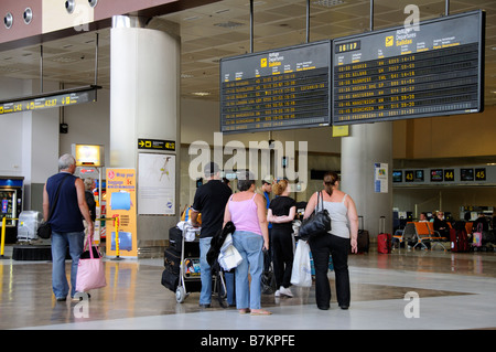 Airport terminal departures board travellers men and women at Reina Sofia Airport in southern Tenerife Canary Islands - Stock Photo