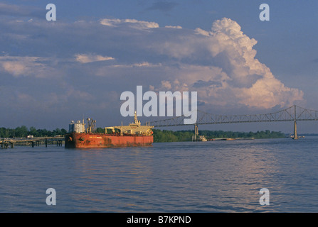 A small tanker takes on refined fuel at a dock on the Mississippi River north of New Orleans - Stock Photo