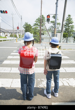 Elementary school students waiting at stoplights - Stock Photo