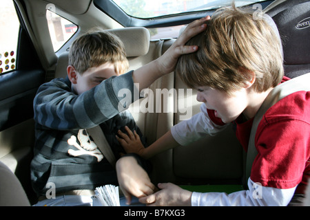 two brothers fighting with eachother in the back seat of car - Stock Photo