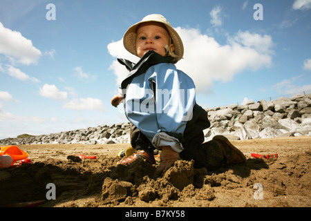 Baby playing on beach in wet sand. Wearing cagoule and hat. - Stock Photo
