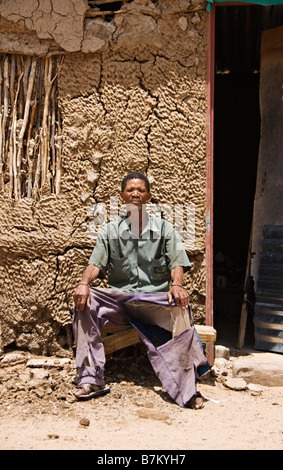 One of the few remaining bushman sitting down in front of his traditional shack the indigenous people of Kalahari - Stock Photo