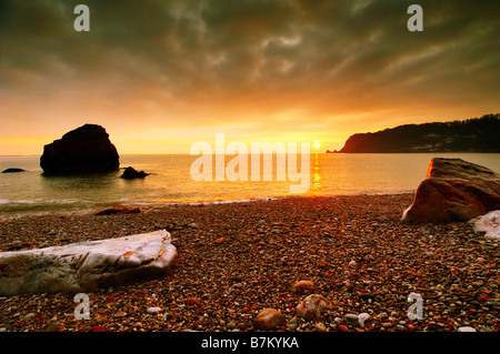 Sunrise from Little Oddicombe Beach in Torquay in South Devon England looking west along the coast - Stock Photo