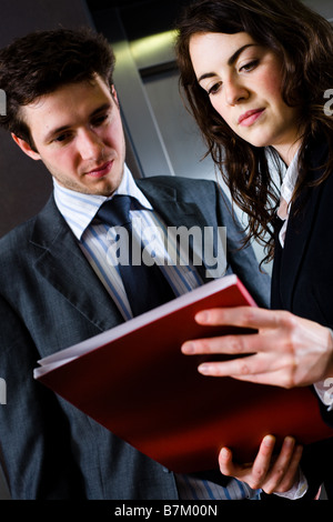 Young businesspeople working together at office corridor looking at red document folder reading reports - Stock Photo