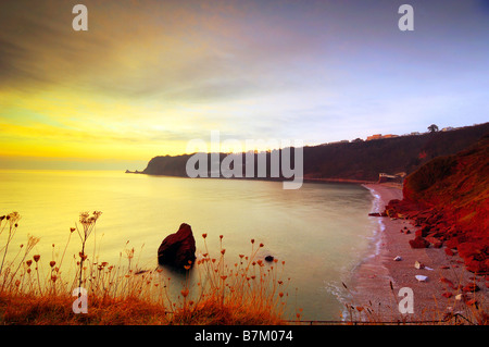 Sunrise from Petitor Point overlooking Little Oddicombe Beach in Torquay in South Devon England looking South along - Stock Photo
