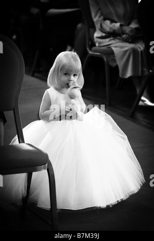 Young flower girl bridesmaid attendant in white princess dress standing in isle holding teddy bear toy wedding day - Stock Photo
