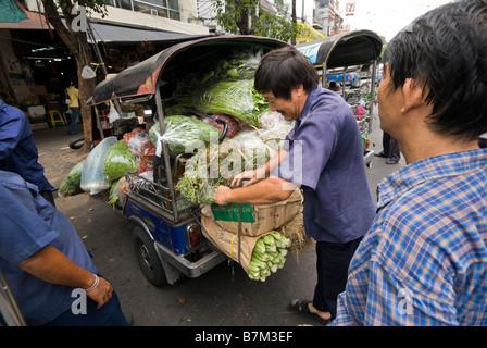 Auto rickshaw driver loading vehicle with vegetables Pak Khlong Talad fresh fruit and vegetable market in Bangkok - Stock Photo