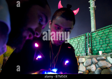 A Sephardic Jew wearing illuminated devil horns at the graveyard compound of Israel Abuhatzeira known as Baba Sali - Stock Photo