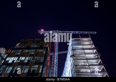 A crane stands tall between two buildings on a construction site at night in south-east London, United Kingdom. - Stock Photo