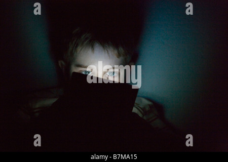 nine year old boy playing nintendo portable ds video game system in the dark, expressing great concentration - Stock Photo