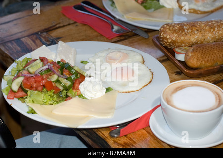 Traditional Israeli Breakfast with two fried eggs yellow cheese salad a fresh roll and a cup of cappuccino - Stock Photo
