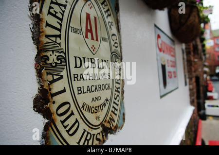 Old, weathered sign advertising Guinness on the wall of the Duke of York pub, Belfast. - Stock Photo