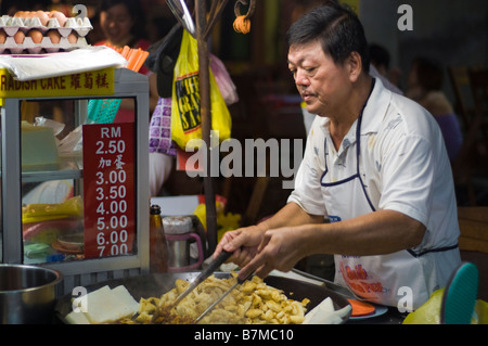 Man making radish cakes in Jonker Street night market, Melaka, Malaysia - Stock Photo