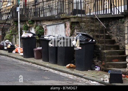 Domestic wheelie bins and bags piled waiting collection on street - Stock Photo