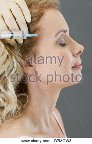 A middle-aged woman receiving a botox injection - Stock Photo