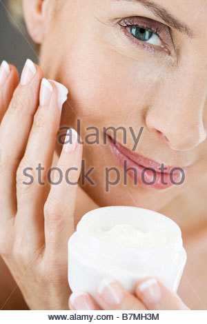 A middle-aged woman holding a pot of moisturising cream - Stock Photo