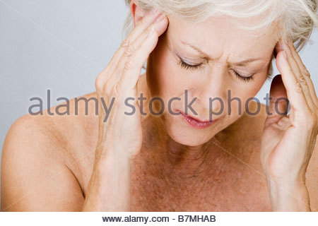 A senior woman with a headache, touching temples - Stock Photo