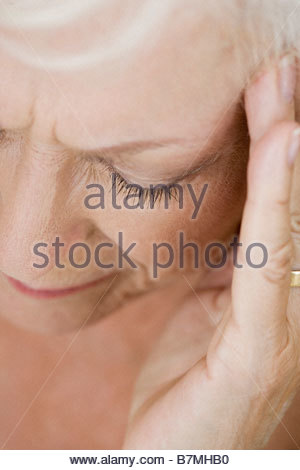 A senior woman with a headache, touching temple - Stock Photo