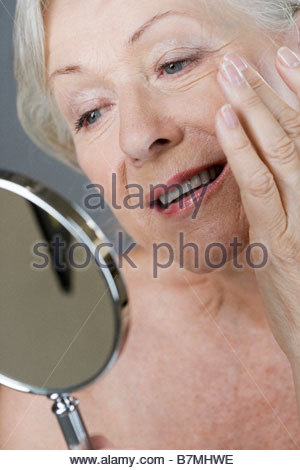 A senior woman looking at her face in the mirror - Stock Photo