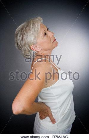 A senior woman with backache - Stock Photo